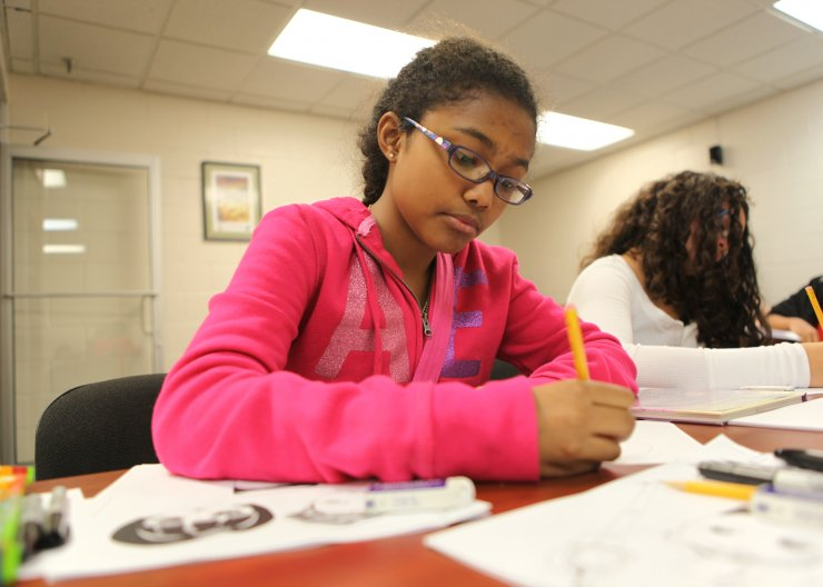 Saturday Academy student working on a comic in a summer camp
