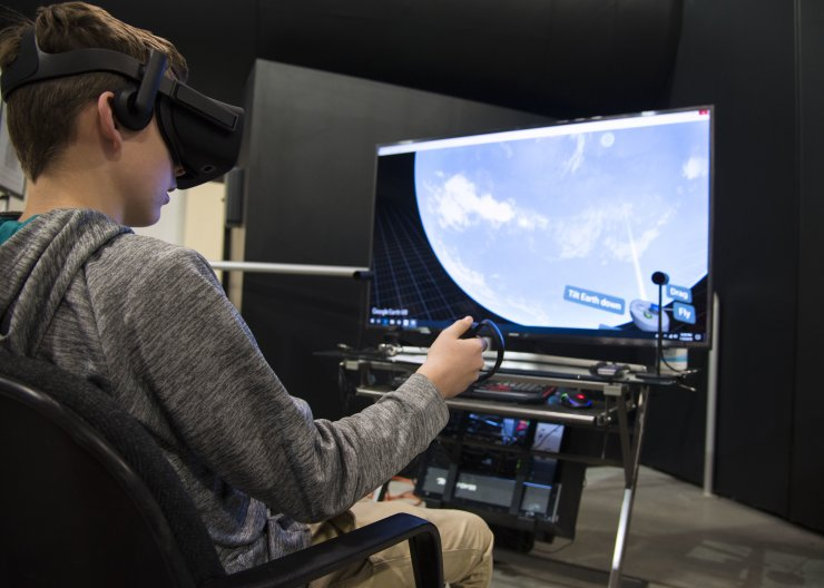 Boy using VR headset to create