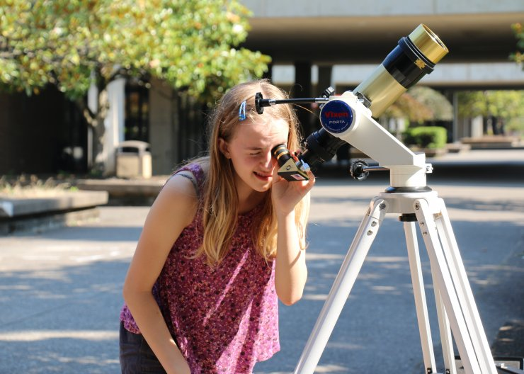Astronomy girl looking through telescope