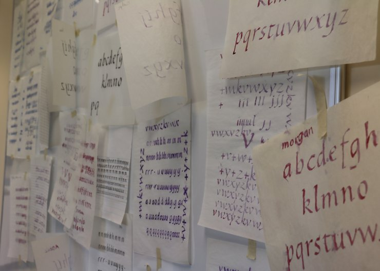 Saturday Academy student's calligraphy work hung on the wall in a summer camp classroom