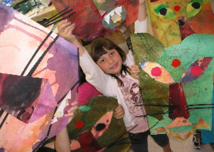 Kid smiling & showing off art made at a Saturday Academy class