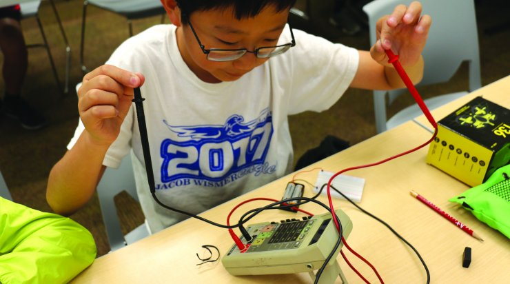 Boy learning about electronics at SA class