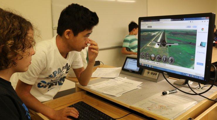Boy students using flight simulator