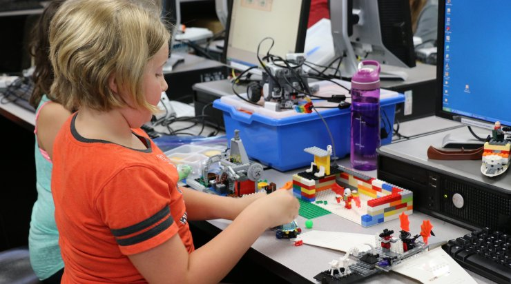 One student building with LEGOs at Saturday Academy