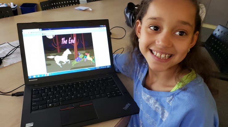 Saturday Academy student proud displaying her computer project with unicorn