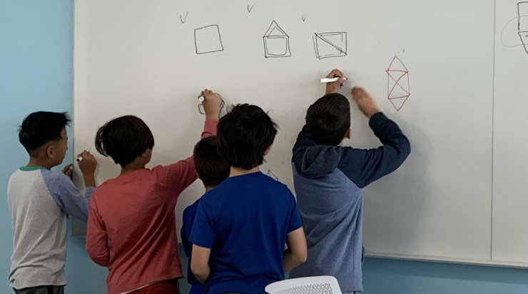 Saturday Academy students working on math problems on a white board