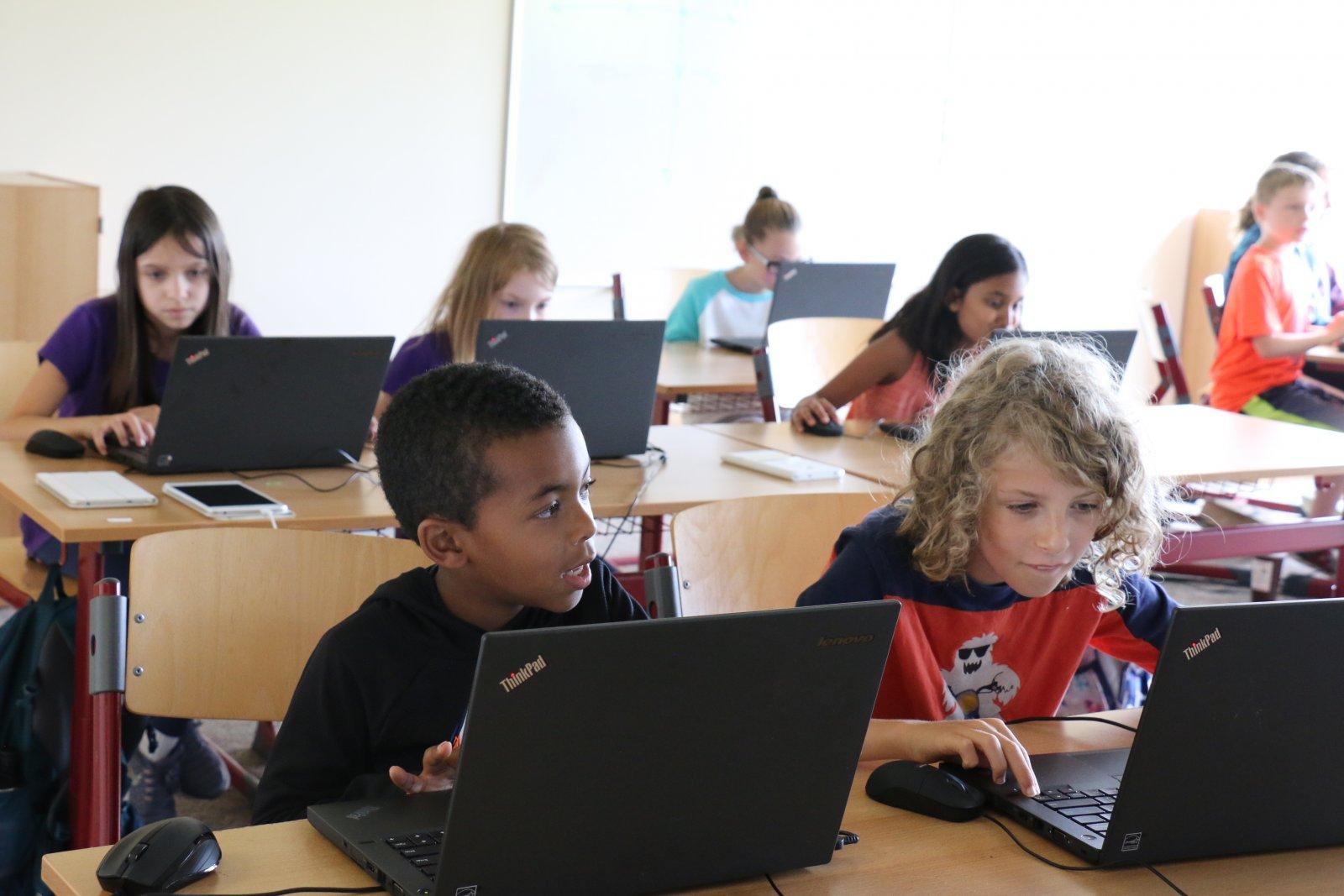 students programming at laptops at Saturday Academy
