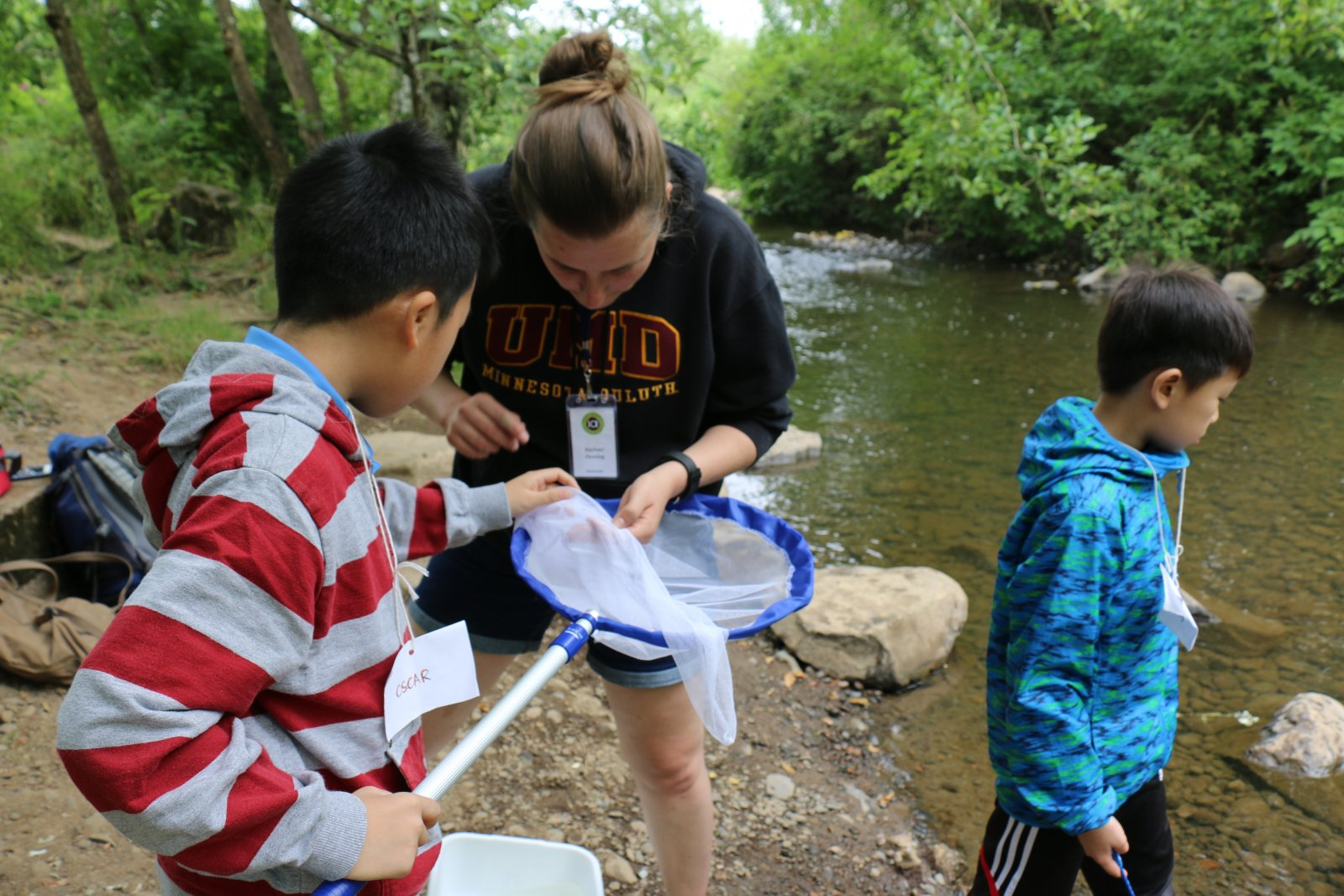 Saturday Academy students working with instructor outside in biology summer camp